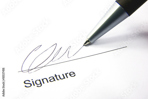 Detail view of the signature box of a contract with a pen.