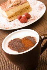 Cappuccino with a chocolate heart and a slice of tiramisu