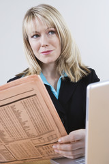 Businesswoman Reading Stock Listings in Newspaper