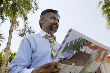 Architect Holding Book with Building Plans