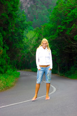 Blond girl standing right in the middle of the mountain road
