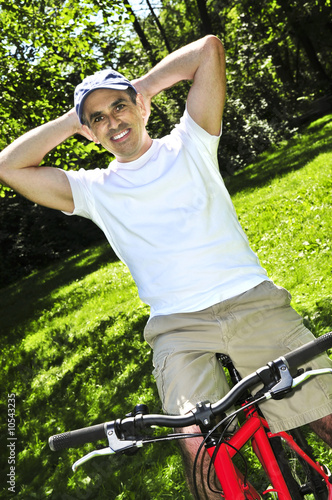 Happy middle aged man riding a bicycle in summer part