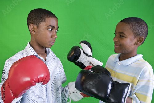 Two African American boys wearing boxing gloves.