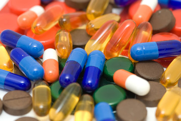 Color pills close up over white
