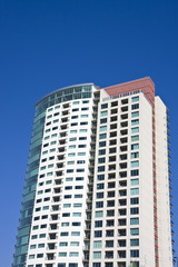 A modern high rise condominium building against a blue sky