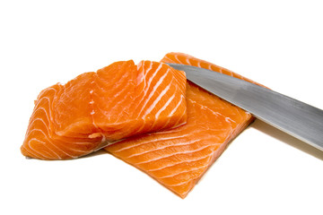 A knife and two salmon fillets on a white background