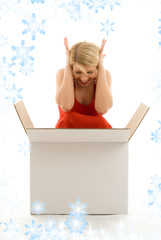 happy girl in red dress with big blank white box and snowflakes