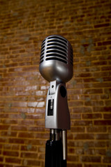 A vintage microphone in front of a brick wall