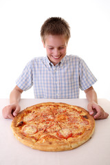 Young boy eating pizza.