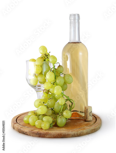 bottle of white wine and grapes in a glass on white background