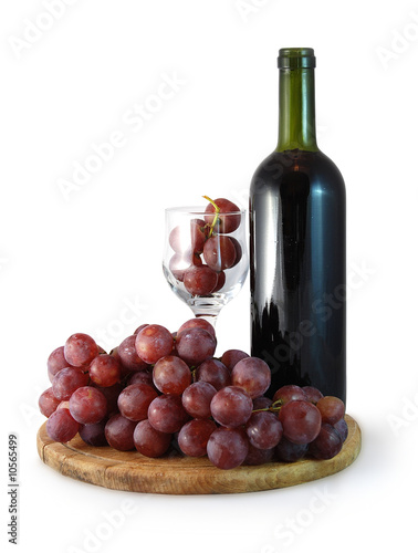 bottle of red whine and glass with red grapes in it