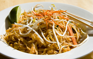 A colorful dish of pad thai noodles with lime and chopsticks