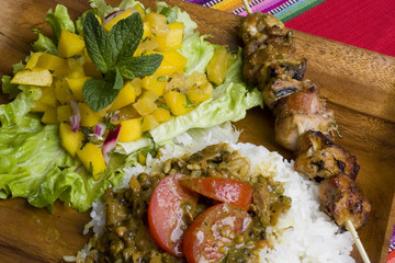 Fresh grilled chicken kebab with mango salsa and curry