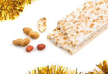 Nougat and peanuts on white background, close up shot.
