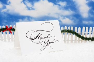 Thank you card sitting on snow with white fence garland