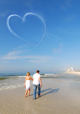 Couple strolling on beach poster