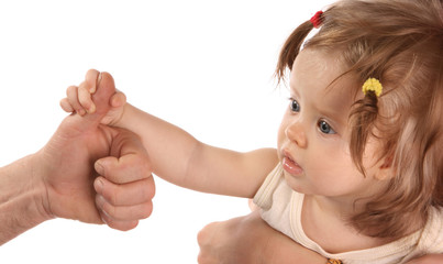 A baby holds on to the finger of hand.