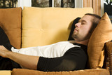 Young man having a nap on couch in living room poster