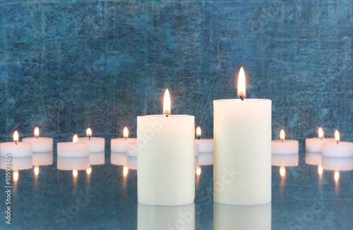 Leinwandbild Motiv Weiße Kerzen vor blauem Hintergrund