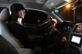 Beautiful young woman driving car at night poster