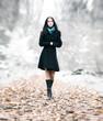 Slim brunette woman walking in a park
