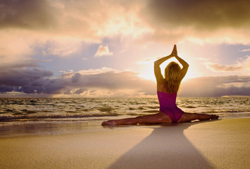 woman doing yoga and stretches on the beach at sunrise.