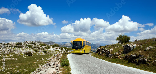 Yellow tourist bus in nature reserve El Torcal