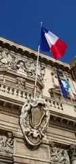 Drapeau tricolore, façade de pierre, Ciel bleu, France.