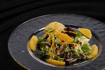 Salad from rukola with leaves of salad and segments of an orange