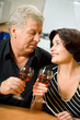 Senior happy couple celebrating with red wine at kitchen