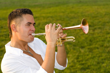 The musician blows the trumpet