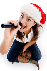 model holding karaoke and wearing christmas hat