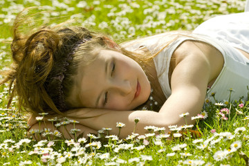 Cute young girl resting in park  between the daisies