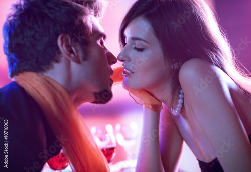 Young kissing amorous couple at celebration