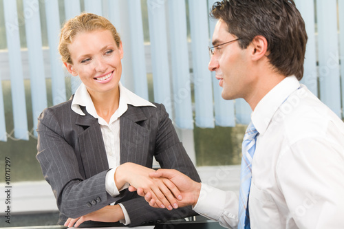 Two businesspeople cheering by handshake or flirting