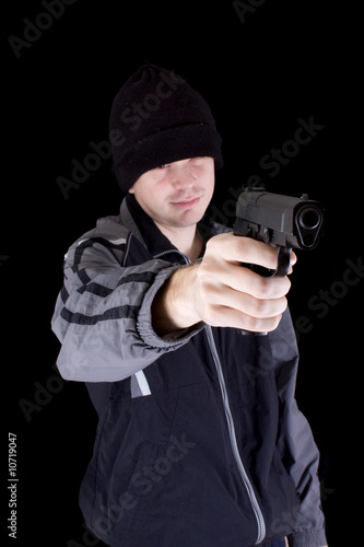 Young man with gun on black background