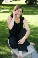 Beautiful Girl in the Park in a Black Dress Talking on the Phone