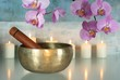 Klangschale mit Orchideenblüten und Kerzen