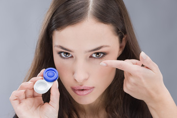 woman holding contact lenses cases and lens in front of her face