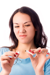 young woman breaking a cigarette and frowning