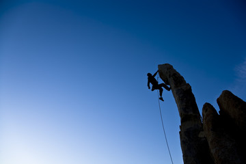 Climber dangling from a pinnacle.