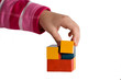 Child hand building a cube of colored blocks