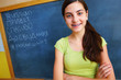 Beautiful young girl with blackboard in background