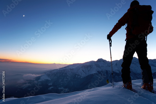 backcountry skier reaching the summit of the mountain - 10772816