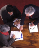 overhead view of three people in a business meeting poster