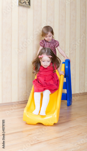 Two adorable girls having fun atop playground slide