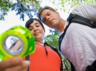 Couple with backpacks looking at compass