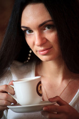 Beautiful young woman enjoying latte coffee in cafe.