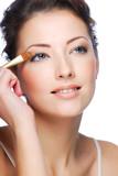 Applying eyeshadow using eyeshadow brush poster