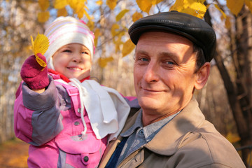 Grandfather with  granddaughter on hands with yellow leafs